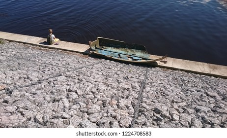 Embankment of the Volga River. The Boy Sits on the Embankment and Looks at the River. Broken Boat. Dark water.