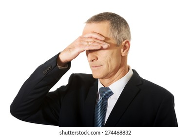 Embarassed businessman covering his face.