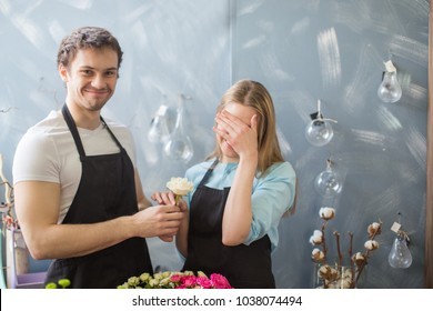 embarrased girl taking white rose from her boyfriend. closing eyes