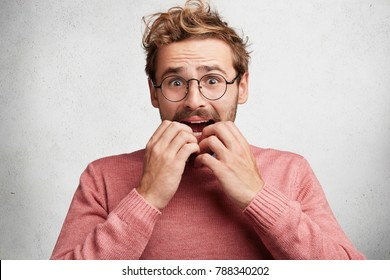 Embarrased nervous male looks scared and worried, bites nails, has sorrorful and frightened expression, expresses negative emotions. Amazed scared young clever man worries before job interview