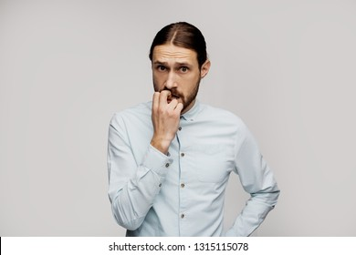 Embarrased nervous seriously man looks worried, bites nails, has sorrorful and frightened expression, expresses negative emotions. Scared young clever business man worries before job interview