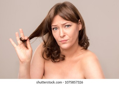Embarrased woman posing on camera and showing her damaged hair. Isolated on white background. Mid age woman over 35 years old concept.