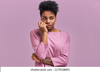 Embarrassed African American woman pursed lips, looks with puzzlement, hears something not clear, dressed in casual top, isolated over lavender background. People and facial expressions.