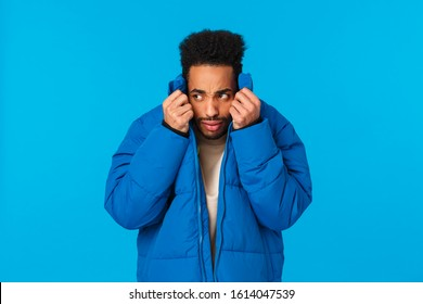 Embarrassed or ashamed guy hiding his face not to be recognized in public. Nervous and alarmed african american man pull collar of padded jacket on face and peeking left, avoiding person