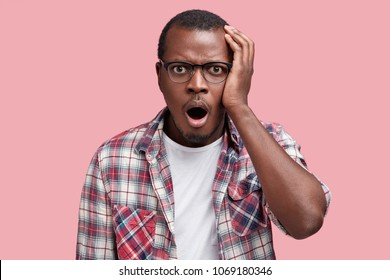Embarrassed attractive African American male with shocked expression, dressed in checkred shirt and eyewear, expresses great amazement, isolated over pink background. Puzzled man poses indoor