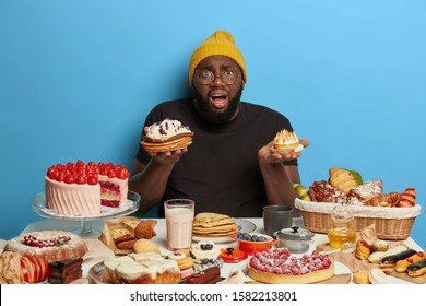 Embarrassed black fat bearded man holds two tasty cakes, cannot make choice what to eat, has tasty sweet breakfast, dressed in casual wear, isolated on blue wall. Weight loss concept. Baked goods