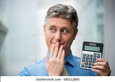 Embarrassed Businessman Showing Zero on Calculator