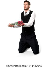 Embarrassed Caucasian man with short dark brown hair in business formal outfit holding flowers - Isolated