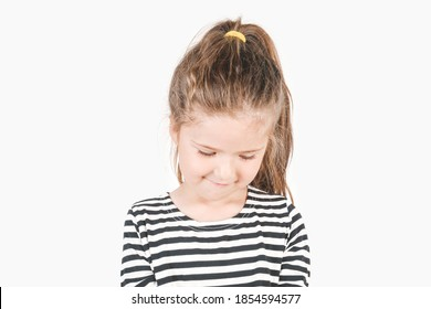 Embarrassed girl looking down with a shy smile. Girl with head tilted forward down. Posing little girl wearing striped shirt.