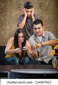 Embarrassed Hispanic teenager behind parents playing video games