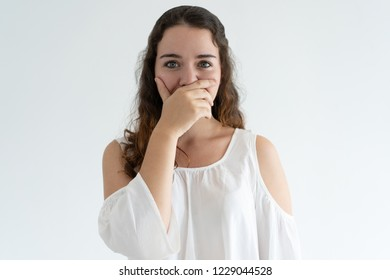 Embarrassed lovely woman covering mouth with hand. Young lady looking at camera. Embarrassment concept. Isolated front view on white background.