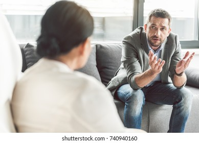 Embarrassed man speaking to psychotherapist