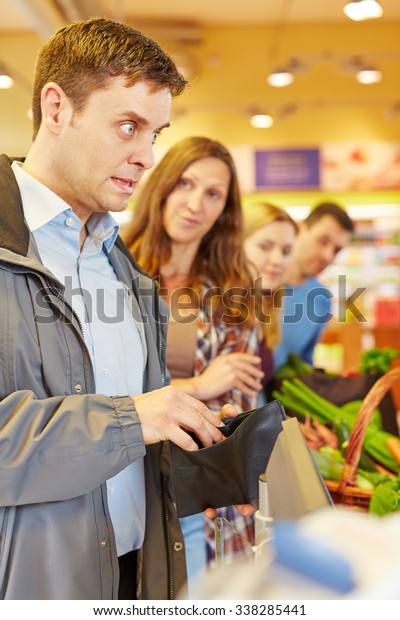 Embarrassed man at supermarket checkout forgot his money for payment
