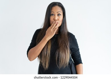 Embarrassed middle-aged woman covering mouth with hand. Lady looking at camera. Embarrassment concept. Isolated front view on white background.