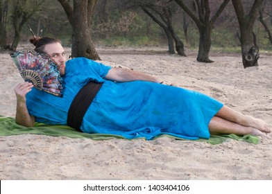 embarrassed transsexual handsome man with make up, hair bun lying on sand in blue kimono, holding hand fan and looking at camera on rug