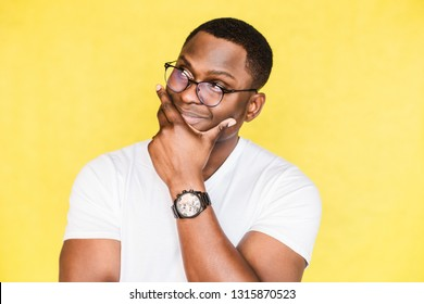 Embarrassed unsure African American man with glasses holds his chin and purses his lips, looks incredulously, tries to make a decision.