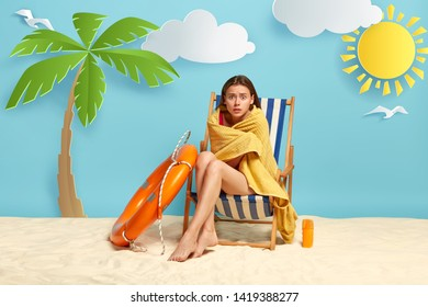 Embarrassed woman covered with yellow towel, poses on deckchair, trembles from cold after swimming in cool water, sunlotion and lifebuoy near, relaxes on beach with sand. Summer rest concept