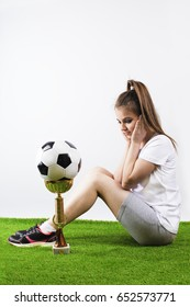 An embarrassed young girl in sports looks at the prize and soccer ball. Gray background