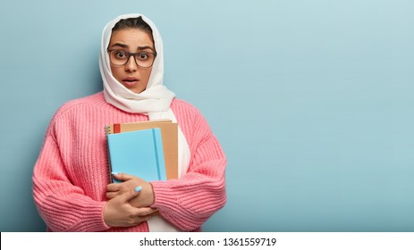Embarrassed young mixed race student has unexpected reaction on groupmates remark, holds notebok and book, prepares for seminar, covers head with white scarf, wears pink jumper, poses in studio