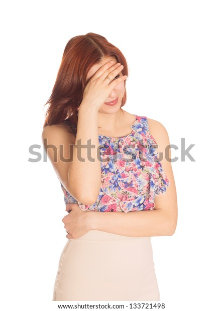 embarrassed young woman covered her eyes with her hand on a white background isolated