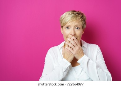 Embarrassed young woman covering her mouth with both hands in an OMG moment over a pink studio background with copy space