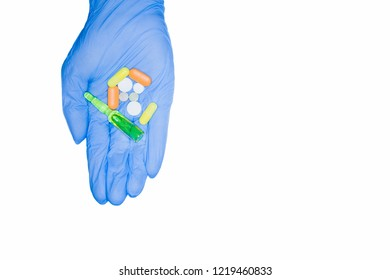 Embezzlement of hospital drugs. Green capsules, pills, ampoule held by hand in medical glove, isolated on white background.