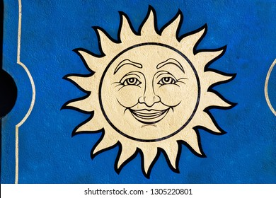 Emblem of smiling sun. Golden sun face symbol with sun rays. Summer weather and heat sign.
