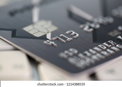 Embossed chipped credit card lying on silver keyboard closeup. Retail sale funds savings atm stash debt visa bankcard customer security pin code management trade earn investment discount concept
