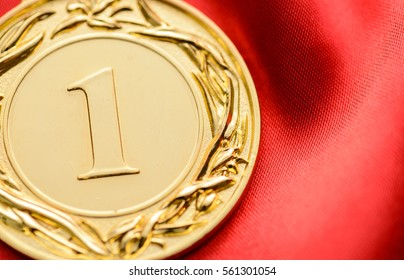Embossed gold winners medallion for the first place in a competition or championship with a large number 1 in the centre on red fabric with copy space