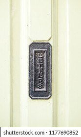 An embossed letter box signage on a wooden door.