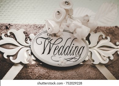 """Embossed printed calligraphy of """"our wedding"""" on a cutout of cardstock and decorated with mini white ribbon roses."""