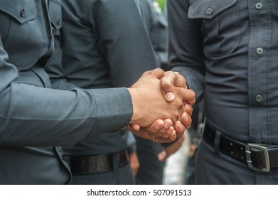 Embrace with handshake on a graduate student's police.
