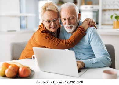 Embraced mature couple surfing the Internet on laptop at home