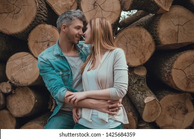 embracing couple in front of cutted trees