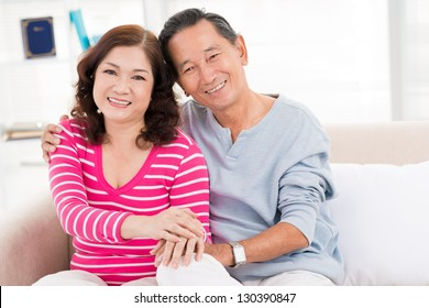 Embracing couple sitting on the sofa indoors
