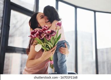 Nimm dich ein. Tochter gratuliert Mutter zu Urlaub und gibt Blumenstrauß.