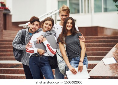 Embracing each other. Group of young students in casual clothes near university at daytime.