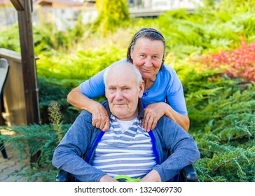Embracing elderly couple outdoors together.