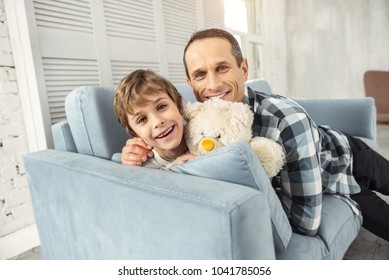 Embracing. Nice cheerful young fair-haired boy smiling and sitting on the couch with his toy and his daddy hugging him