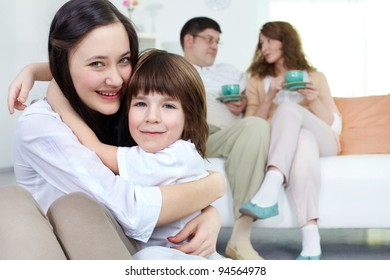 Embracing siblings looking at camera with their parents sitting on sofa at background