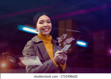 Embracing a technological future concept. A beautiful young Asian woman is being surrounded by a cyberpunk environment where all technology apps are projected as holograms from her phone around her.