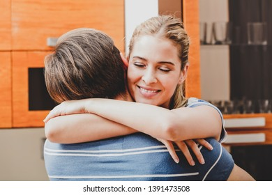 Embrancing couple. Woman is hugging her boyfriend in home interior.