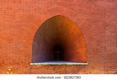 An embrasure or arch window in the red brick wall of the castle. Fragment of the wall of the Peter and Paul fortress.