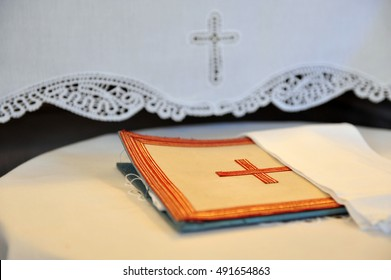 Embroidered cross in orange beige canvas.