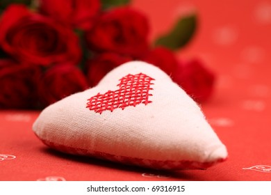 Embroidered fabric heart and red roses on red background. Shallow dof