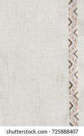 Embroidered fragment on flax by brown and beige cotton threads. Embroidery texture flat stitch. Ukrainian ethnic ornament.