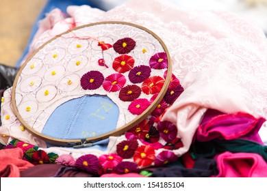 Embroidered handmade flowers on fabric. Latin America ornament.
