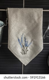 Embroidered lavender on a linen kitchen towel close up