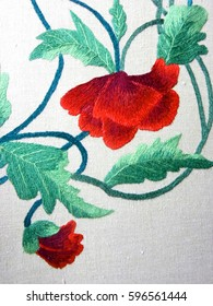 embroidered poppy flower on white fabric, Ukrainian folk embroidery, decorated fabric