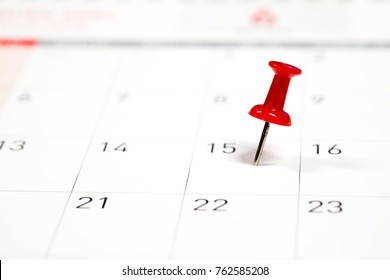 Embroidered red pins on a calendar on the 15th with selective focus